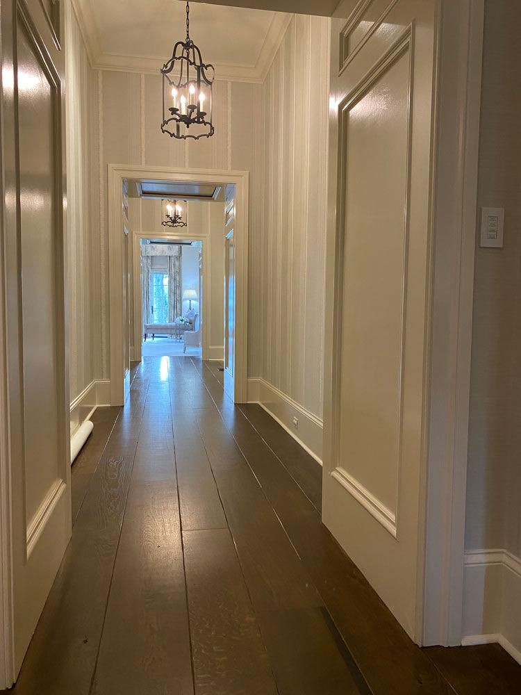 long white hallway with plank flooring